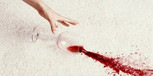 Womans hand reaching for spilled glass of red wine on carpet